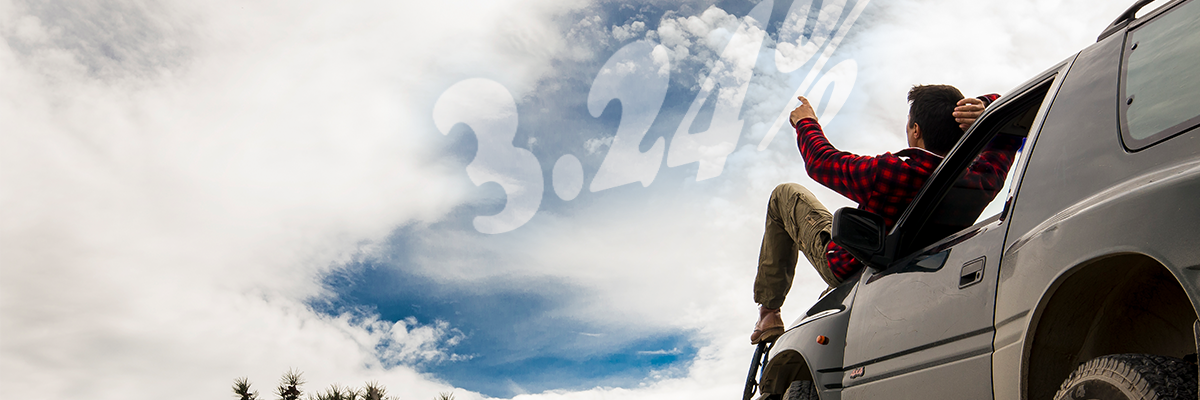 man in flannel shirt sitting on hood of his car pointing at auto rate in the clouds