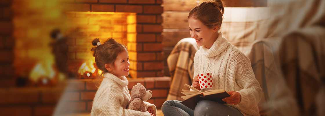 mother and daughter reading a book and sharing cocoa in front of the fire