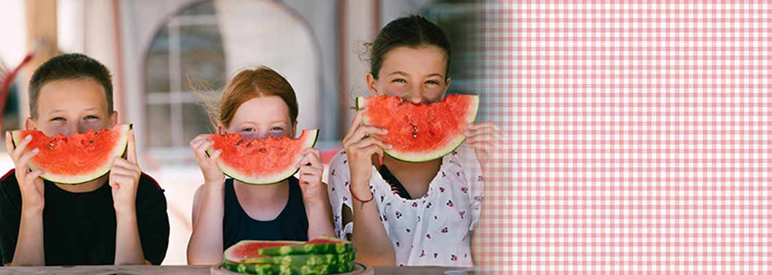 3 kids holding slices of watermelon like smiles