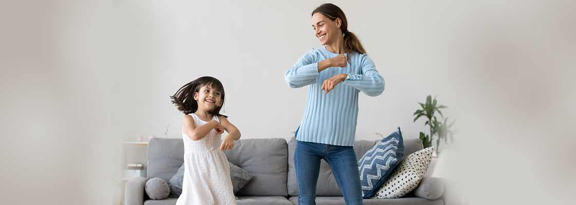mom and daughter dancing in living room surrounded by moving boxes