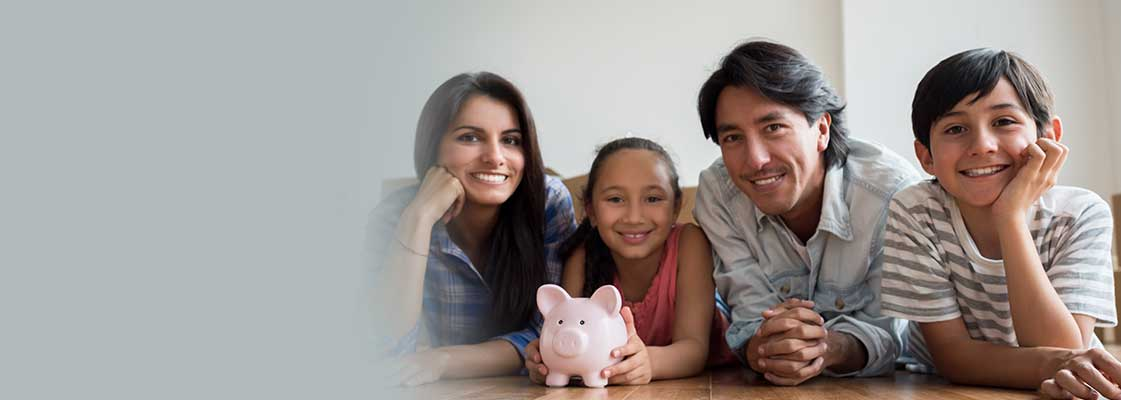 Family posing on living room floor holding a piggy bank with the savings from their home loan with Utah Heritage Credit Union.
